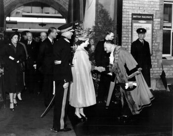 Queen Elizabeth II, with the Duke of Edinburgh pictured just behind, being greeted by the Mayor of Lincoln Councillor Leslie Priestley as they arrived by Royal Train in to Lincoln Central Station (directly next door to St Mary-le-Wigford Church) before officially opening Pelham Bridge, on 27th June 1958. This was their first visit to the City.