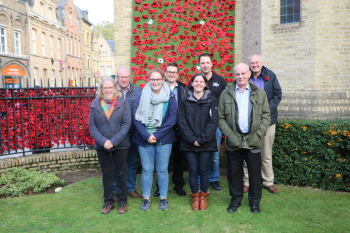 The Band, clockwise from front right in front of part of the poppy display at St George's Memorial Church, Ypres
