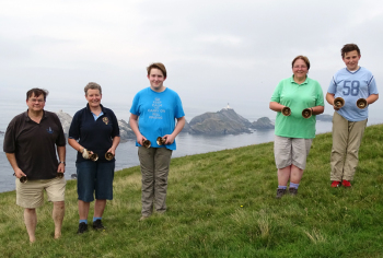 The band, L-R, with Muckle Flugga in the background between the ringers of 5-6 and 7-8.